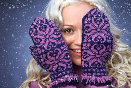 beautiful blonde girl covers her face with mittens on the snow