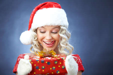 beautiful young blonde girl in santa claus hat smiles for christmas card. Standard-Bild