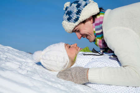 young couple playing and kissing on snow hill in winter Standard-Bild