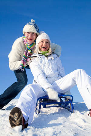 young couple having fun riding on a sled on a winter resort