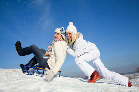 young couple having fun riding on a sled in the snow resort
