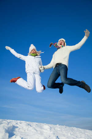 young couple having fun jumping on snowy hill in winter