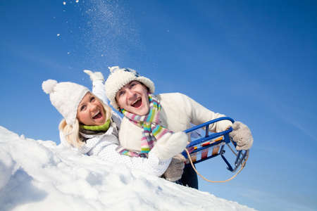 young couple having fun rolling down the hills in the winter sleigh