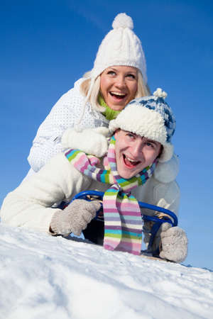 young couple having fun riding on a sled on a snowy hill