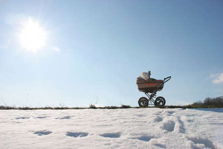 stroller with baby is on path of snow cover of the park under bright sun Standard-Bild