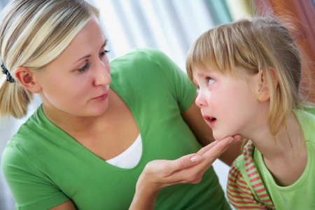 young blonde mother lovingly communicates with her little crying daughter at home.