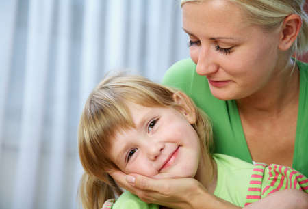 Young blonde mom tenderly hugs her little daughter at home.