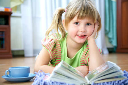 Portrait of a little girl reading a book at home Imagens