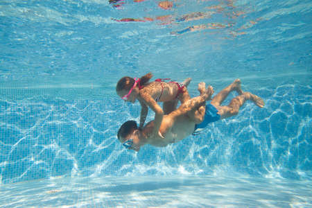 underwater photo of young dad with little girl in swimming pool