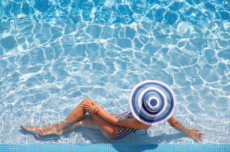 Unrecognizable woman in big hat relaxing on the swimming pool Imagens