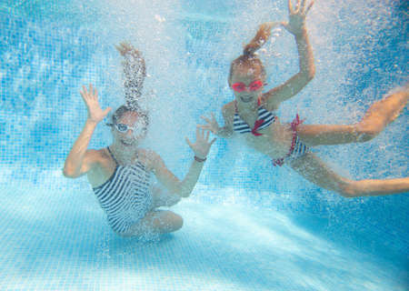 underwater photo of young mother with little girl in swimming pool Imagens