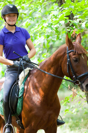 Portrait of young horsewoman on red horse Imagens