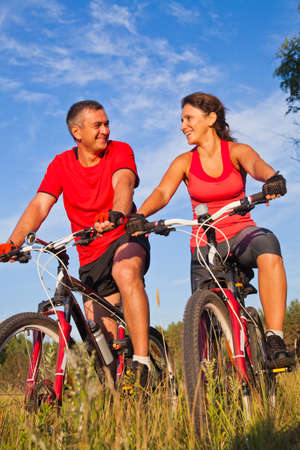 happy mature couple riding a bicycle in the green park