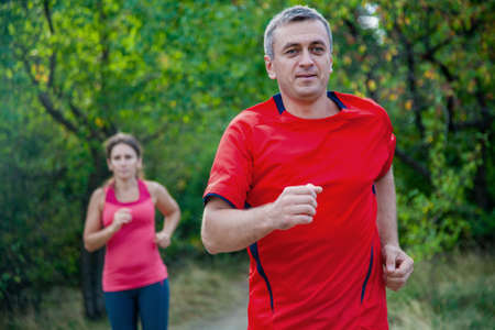 Pair of elderly people jogging on a summer day Imagens