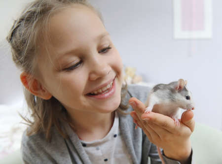Little girl cute plays and makes friends with a white tamed mouse at home.