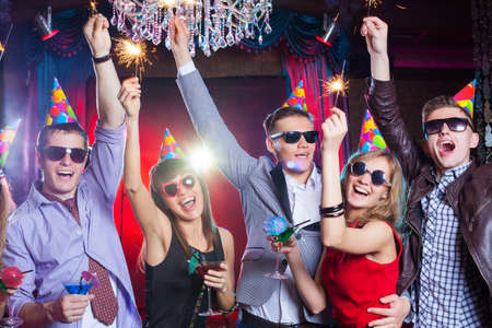 cheerful young company celebrates in a nightclub Imagens
