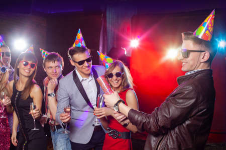 Cheerful young people showered with confetti on a club party. Stock Photo