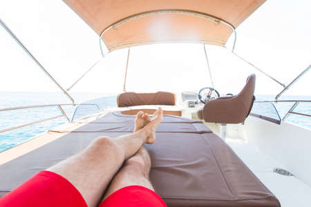 Only legs of man enjoys relaxing on a yacht at sea