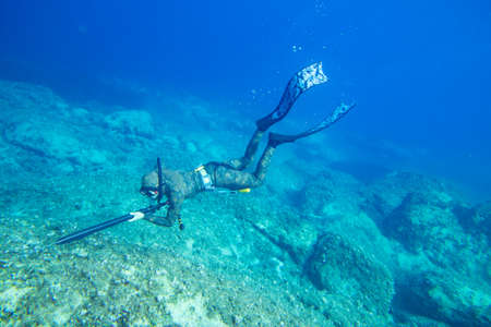 Underwater hunter with gun dives into the depths of the sea
