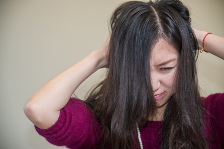 problem: Young woman holding her head looking frustrated
