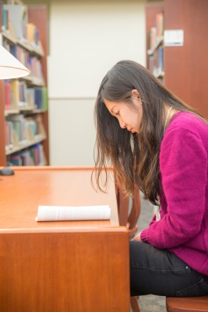 Woman with book studying in library