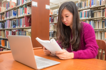 Woman with book and laptob studying in library Imagens