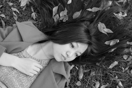 spreaded: Young woman laying on grass with spreaded hair
