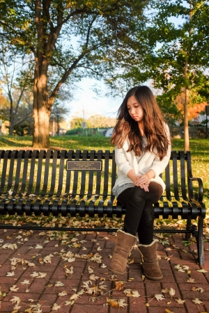 curls: lonely young woman sitting on a steel bench