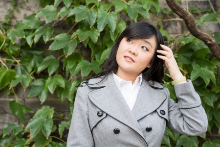 Young Asian woman standing next to leafs on a wall and smiling Stock Photo - 23669360