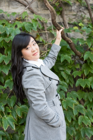 Young Asian woman standing next to leafs on a wall holding a branch