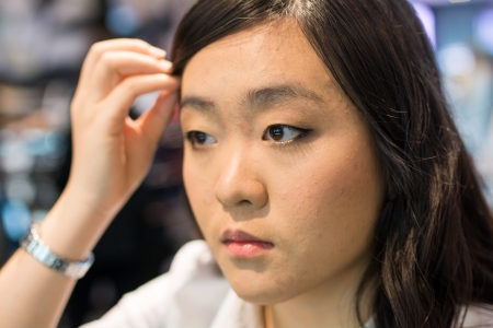 womna: Young Asian womna checking herself while applying cosmetics
