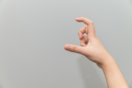 Human hand holding imaginary card with two fingers on light gray background photo