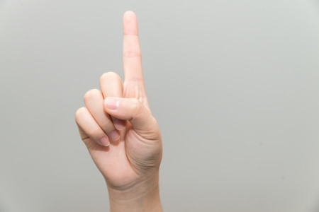 grabbing at the back: Human hand with one finger sticking up on light gray background