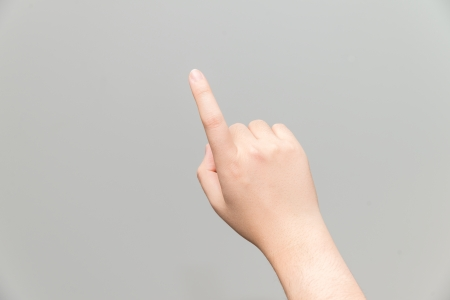 grabbing at the back: Human hand with one finger touching imaginary tablet on gray background
