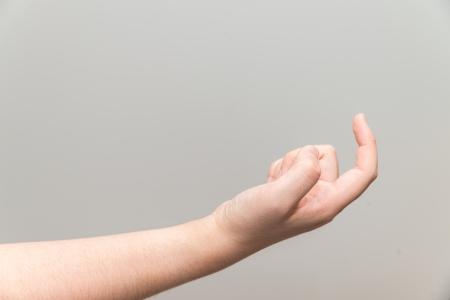grabbing at the back: Human hand with curl index finger on light gray background Stock Photo