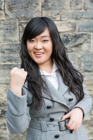 Portrait of successful young woman in front of a stone wall holding up fist
