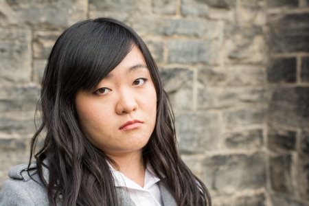 Portrait of young girl in front of a stone wall looking upset photo