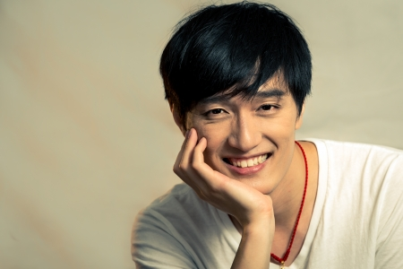 asian model: Young man supporting chin and smiling, with fashion tone and background