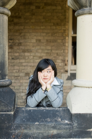 leaning forward: Young woman leaning forward next to stone pillars Stock Photo
