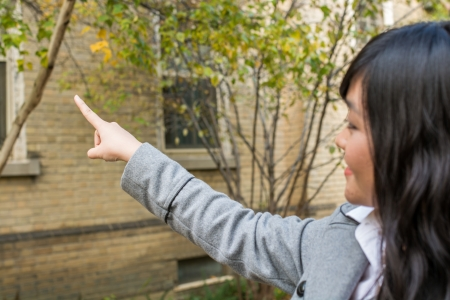 self discovery: Portrait of young attractive girl pointing at something on the trees at the side of a road Stock Photo