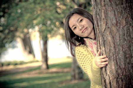 peaking: portrait of shy young woman peaking from behind a tree and smiling