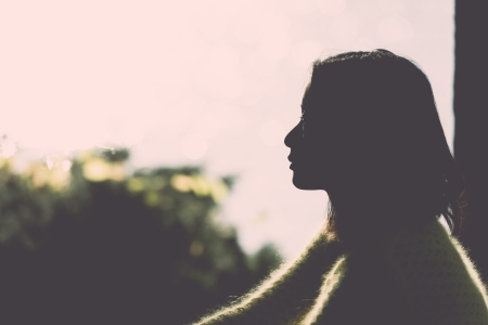 Silhouette portrait of lonely young woman sitting during dusk time