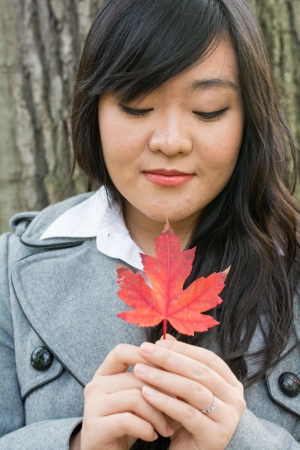 Autumn portrait of cute young woman in front of a maple tree holding a maple leaf with eyes closed