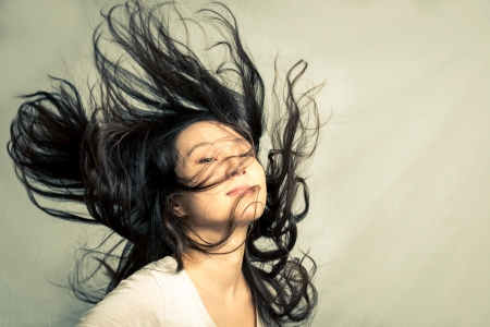 flicking: Young woman flicking her hair and posing, with fashion tone and background Stock Photo