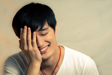 Young man covering his face and smiling, with fashion tone and background