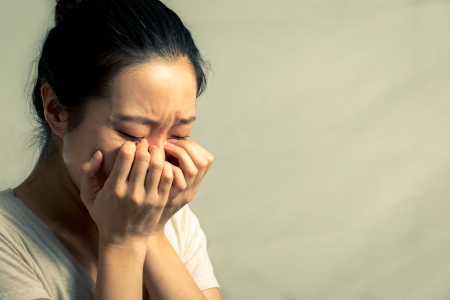 hiding: Portrait of young woman crying desperately, with fashion tone and background Stock Photo
