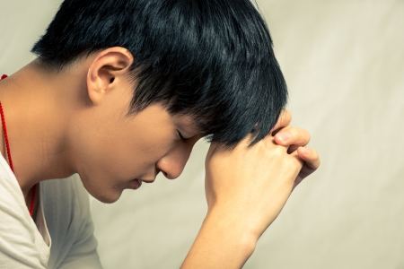 Young man supporting his head looking depressed, in fashion tone and background photo