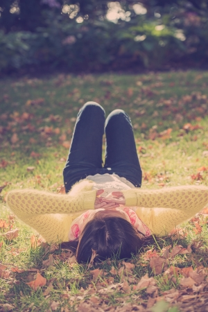Unique top view of young woman laying in grass with a bunch of fallen leafs