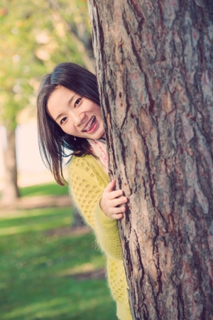 peaking: portrait of shy young woman peaking from behind a tree and sticking out her tougue