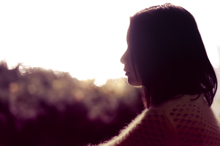 Silhouette portrait of lonely young woman sitting during dusk time Standard-Bild